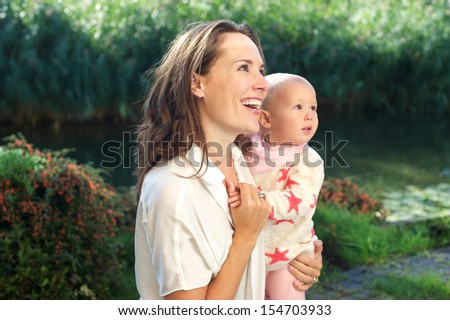 Closeup portrait of a happy mother smiling with cute baby outdoors