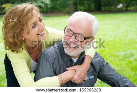 Closeup portrait of a happy older couple laughing outdoors - stock photo