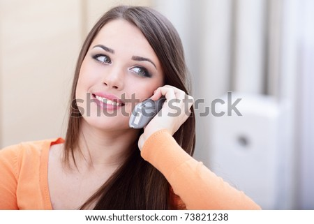 Closeup portrait of a happy woman on phone at home looking at copyspace - stock photo
