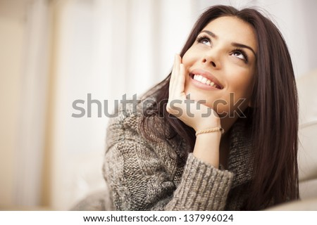 Closeup portrait of a Happy young beautiful woman relaxing at home - stock photo
