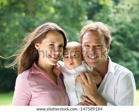 Closeup portrait of a happy young family smiling with baby - stock photo