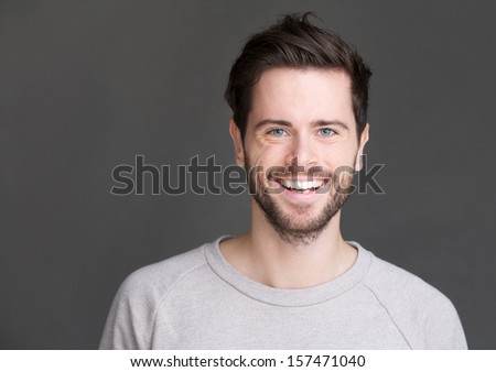 Closeup portrait of a happy young man smiling on gray background - stock photo