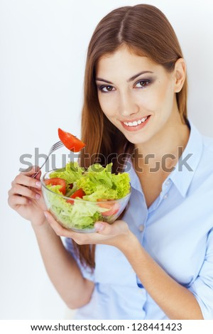 Closeup portrait of a happy young woman eating a fresh salad