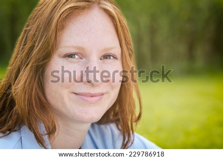 Closeup portrait of a happy young woman in nature looking at the camera.