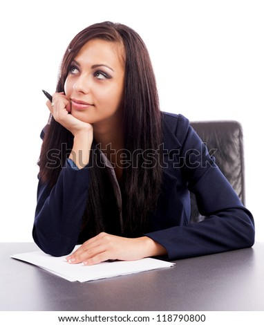 Closeup portrait of a latin businesswoman thinking while sitting at desk isolated on white background - stock photo