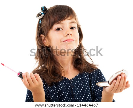 Closeup portrait of a little girl using lipstick while looking in the mirror