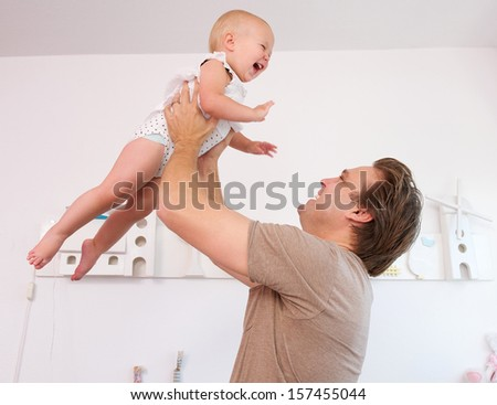Closeup portrait of a loving father playing with cute baby at home