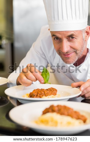 Closeup portrait of a male chef garnishing food in the kitchen