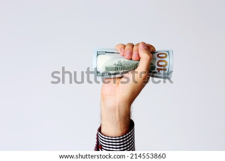 Closeup portrait of a male hand raised up with bill of dollars