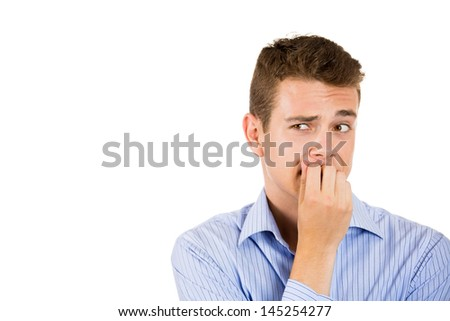 Closeup portrait of a man biting his nails and looking to the side with a craving for something or anxious, isolated on white background with copy space