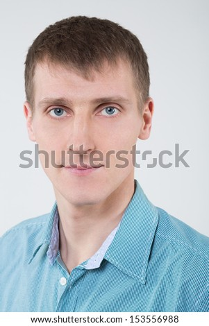 Closeup portrait of a man in a shirt with blue eyes - stock photo