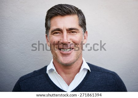 Closeup portrait of a man in his 40s, smiling candidly at the camera while posing outdoors against a textured white wall. His demeanor is pleasant and approachable - stock photo