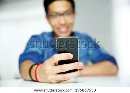 Closeup portrait of a man using smartphone. Focus on smartphone. - stock photo