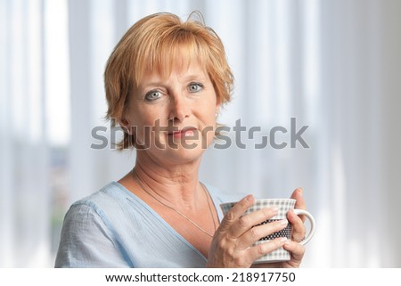 Closeup portrait of a mature woman at home, looking at camera and holding a coffee mug