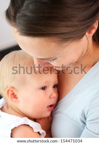 Closeup portrait of a mother holding baby close to chest