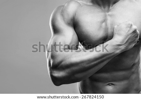 Closeup portrait of a muscular man showing his biceps - stock photo