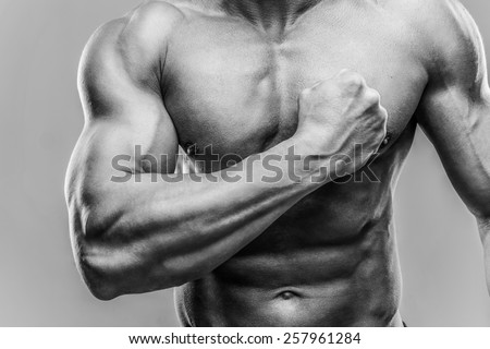 Closeup portrait of a muscular man showing his biceps. HDR monochrome. - stock photo