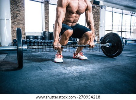 Closeup portrait of a muscular man workout with barbell at gym - stock photo