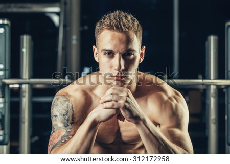 Closeup portrait of a muscular man workout with barbell at gym. He is sitting in the frame view, thinking. - stock photo