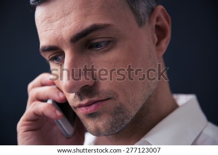 Closeup portrait of a pensive businessman talking on the phone and looking away
