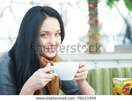 Closeup portrait of a pretty young female having a cup of coffee while resting at cafe - stock photo