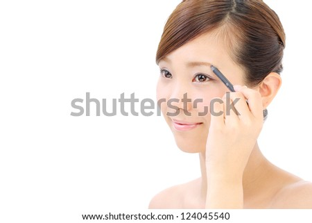 Closeup portrait of a pretty young girl applying eyeliner - stock photo
