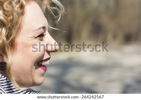Closeup portrait of a pretty young woman with blond curly hair laughing out loud