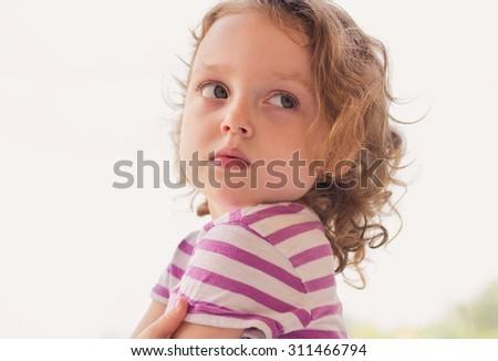 Closeup portrait of a sad little girl standing near the window - stock photo
