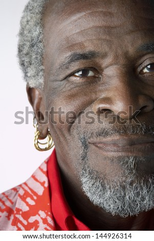 Closeup portrait of a senior African American man with earrings against white background - stock photo