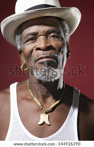 Closeup portrait of a senior man wearing fedora and medallion - stock photo