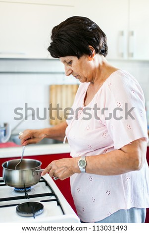 Closeup portrait of a senior woman preparing food on a stove in a kitchen