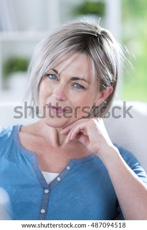 Closeup  portrait of a senior woman, she is pretty and smiling. her hairs are grey. she is in the foreground. she is wearing a blue shirt. the light is on her. she is looking at camera