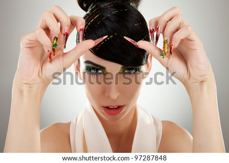Closeup portrait of a serious lady with colorful eye makeup showing her big nails - stock photo