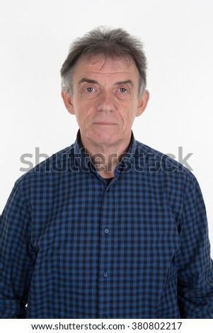 Closeup portrait of a serious senior man looking directly into the camera standing outdoors amongst trees with copyspace