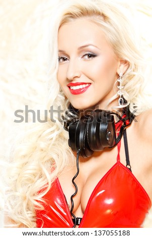 closeup portrait of a sexy happy woman posing in headphones over white
