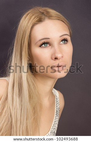 Closeup portrait of a sexy young female fashion model posing against grey background - stock photo