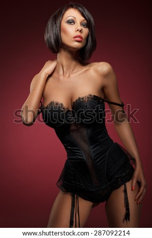 closeup portrait of a sexy young woman in black corset against red wine background - stock photo