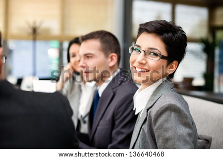 Closeup portrait of a smart young businesswoman smiling and her colleagues working