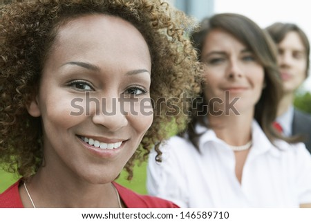 Closeup portrait of a smiling African American woman with blurred friends in background - stock photo