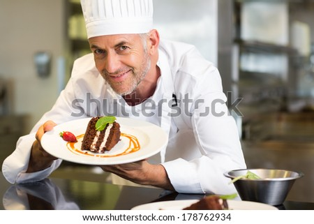 Closeup portrait of a smiling male pastry chef with dessert in the kitchen - stock photo