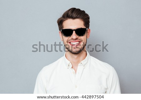 Closeup portrait of a smiling man wearing glasses looking at camera isolated on a gray background - stock photo