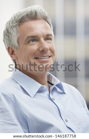 Closeup portrait of a smiling middle aged businessman looking up - stock photo
