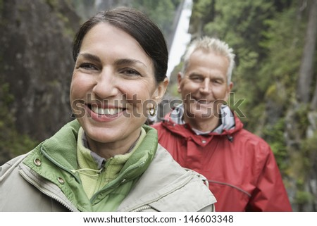 Closeup portrait of a smiling middle aged woman and woman against waterfall - stock photo