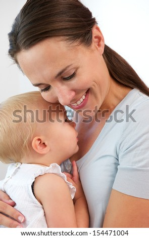 Closeup portrait of a smiling mother hugging cute baby girl