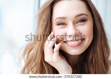 Closeup portrait of a smiling woman talking on the phone and looking at camera - stock photo