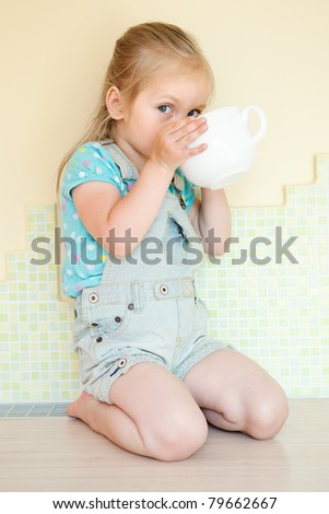 Closeup portrait of a smiling young girl drinking from a cup - stock photo