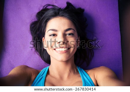 Closeup portrait of a smiling young woman lying on the yoga mat at gym. Looking at camera - stock photo