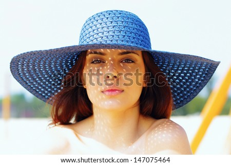 Closeup portrait of a teen girl resting on the beach in hat