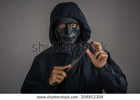 Closeup portrait of a threatening mafia man, holding a knife in his hands,Thief in mask ,representing the concept of danger.studio shot isolated on gray background.