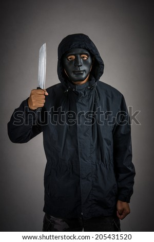 Closeup portrait of a threatening mafia man, holding a knife in his hands,Thief in mask ,representing the concept of danger.studio shot isolated on gray background. - stock photo